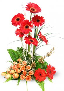Arrangement of Red Gerberas and Orange Roses nicely decorated with fillers and greens.